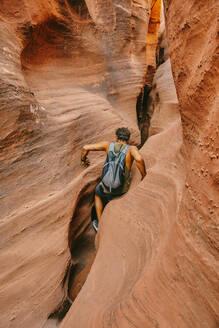 Young man exploring narrow slot canyons in Escalante, during summer - CAVF88929
