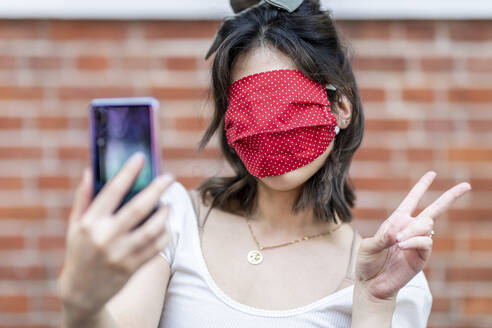 Close-up of woman's face covered with mask taking selfie against brick wall - WPEF03345