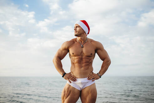 Shirtless macho man wearing Santa hat standing against sea - MIMFF00223
