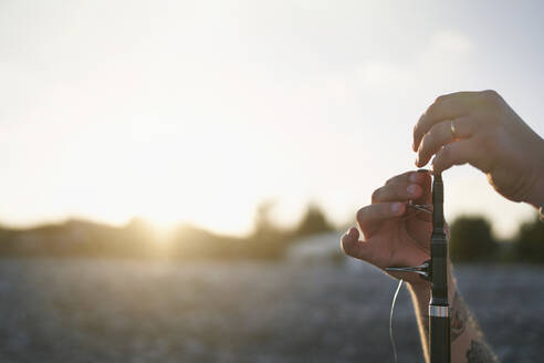 Hands of mid adult man preparing fishing rod at beach against sky during sunset - SASF00089