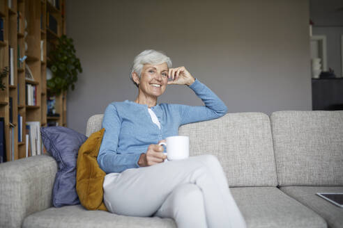 Smiling senior woman sitting on sofa holding coffee cup at home - RBF07795