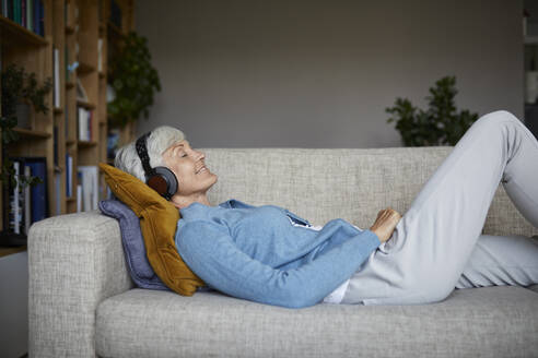 Senior woman listening to music while lying down on sofa at home - RBF07804