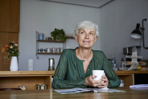 Thoughtful senior woman sitting with coffee cup at home - RBF07831
