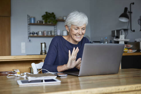 Active senior woman doing high five on video call while using laptop at home - RBF07852