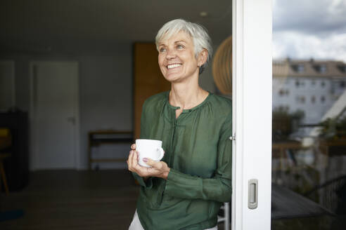 Senior woman looking away standing with coffee cup by window at home - RBF07861