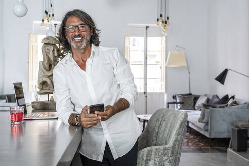 Smiling man using smart phone while standing by counter at home - DLTSF01158