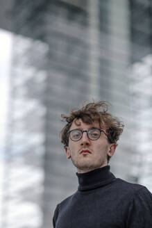 Close-up of serious young man wearing eyeglasses against building - OGF00565