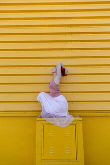 Ballerina with arms raised crouching while dancing on seat against yellow wall - TCEF01077