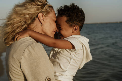 Grandmother nuzzling grandson while carrying him at beach during sunset - ERRF04347