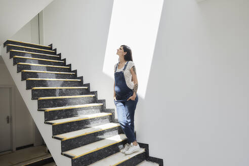 Pregnant woman with hands in pockets standing on staircase - MJFKF00672