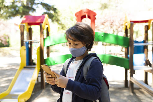 Schoolboy wearing mask using smart phone while standing in schoolyard - VABF03464