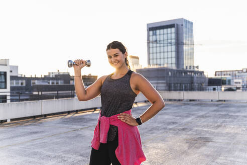 Smiling young woman lifting dumbbell while standing on terrace against clear sky - UUF21411