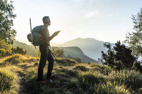 Man using mobile phone while standing on mountain against sky at sunrise, Orobie, Lecco, Italy - MCVF00585