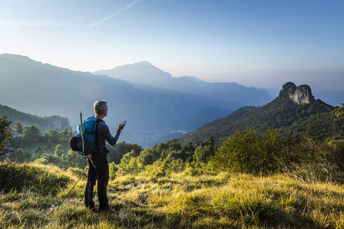 Man with backpack using mobile phone standing on mountain during sunrise, Orobie, Lecco, Italy - MCVF00588