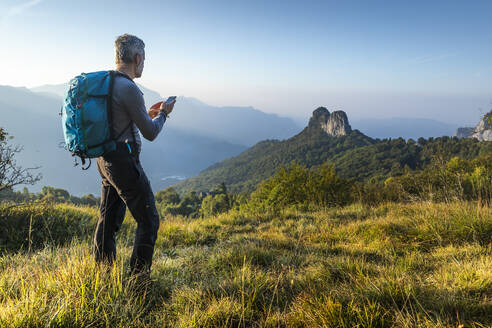 Mature man using smart phone while hiking on mountain at sunrise, Orobie, Lecco, Italy - MCVF00591