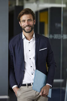 Smiling businessman holding document while standing at office - RBF07876