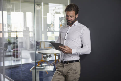 Businessman using digital tablet while leaning on wall at office - RBF07879