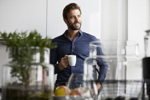 Businessman drinking coffee while standing at cafeteria - RBF07885