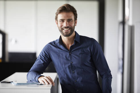 Businessman smiling while leaning on desk in office - RBF07888
