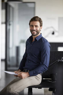 Smiling businessman holding paper while sitting on desk in office - RBF07894