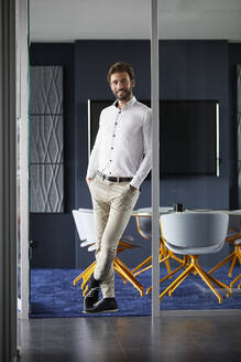 Businessman leaning on glass wall in office - RBF07897