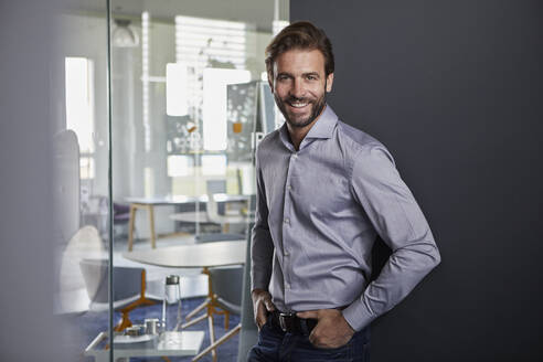 Businessman smiling while leaning on wall in office - RBF07903
