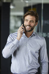 Businessman smiling while talking on mobile phone in office - RBF07915