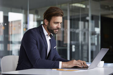 Businessman working on laptop while sitting at office - RBF07918