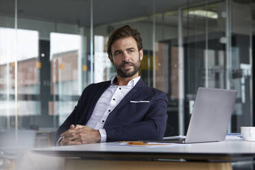 Thoughtful businessman with laptop sitting on chair in office - RBF07921