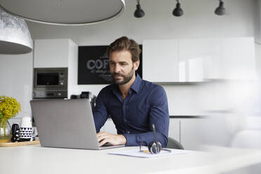 Man working on laptop while sitting at cafeteria - RBF07930