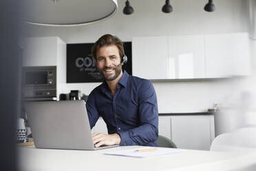 Businessman wearing in ear headphone talking while working on laptop at cafeteria - RBF07933