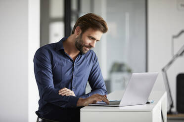 Businessman using laptop while standing at desk in office - RBF07936