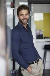 Man with hands in pockets smiling while leaning on wall in office - RBF07939