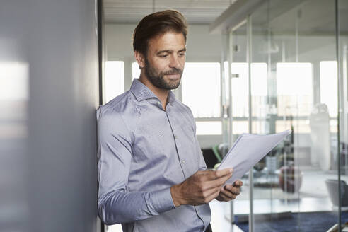 Businessman reading document while leaning on wall in office - RBF07942