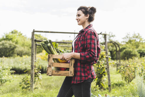 Young woman carrying vegetables in crate while walking against sky at garden - UUF21474