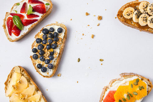 Studio shot of five slices of bread with fresh fruits - FLMF00298