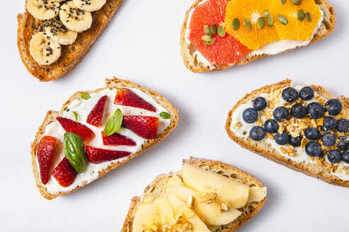 Studio shot of five slices of bread with fresh fruits - FLMF00301