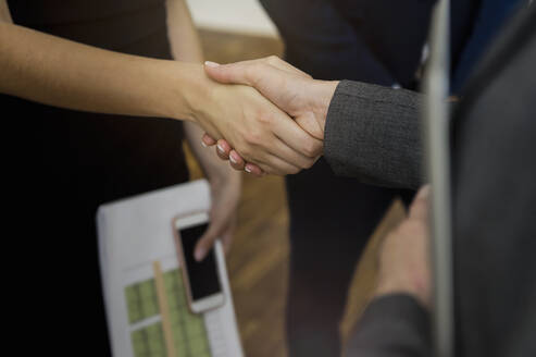 Close-up of colleagues giving handshake in office - BMOF00401