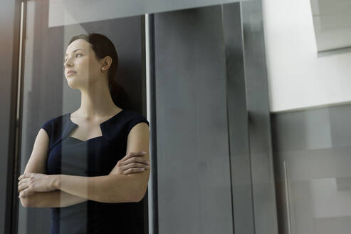 Thoughtful businesswoman with arms crossed standing in office seen through glass door - BMOF00413