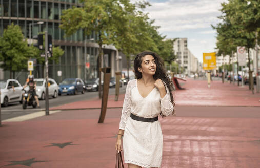 Young woman wearing white dress looking away while walking on footpath in city - BFRF02290
