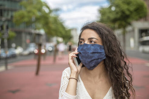 Close-up of young woman wearing mask talking over mobile phone in city - BFRF02293