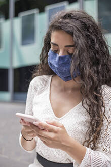 Close-up of young woman wearing face mask using mobile phone while standing in city - BFRF02296