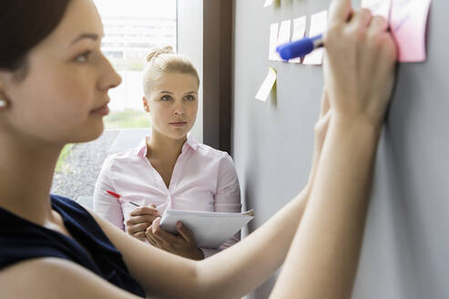 Businesswoman writing on adhesive note stuck on wall while discussing with colleague in office - BMOF00427