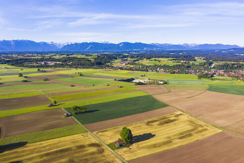 Germany, Bavaria, Huglfing, Drone view of countryside fields in Alpine foothills during spring - SIEF10044