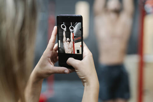 Close-up of young woman photographing boyfriend hanging on rings in gym - JCZF00226