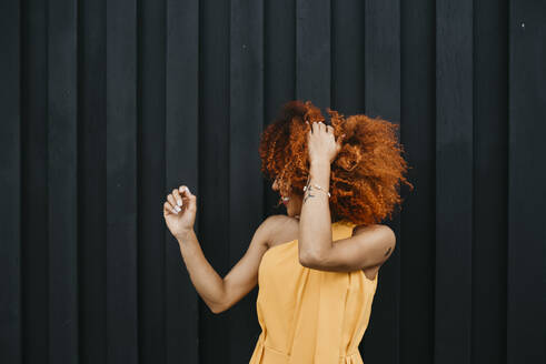 Cheerful young woman shaking hair while standing against wall - DSIF00115