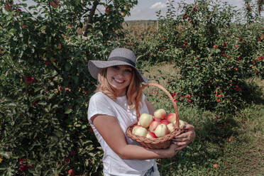 Smiling woman wearing hat holding apples in basket while standing at orchard - OGF00587