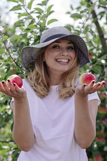 Cheerful woman wearing hat holding apples while standing in farm - OGF00590