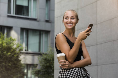Smiling beautiful woman holding coffee cup using smart phone while standing against building in city - BMOF00442