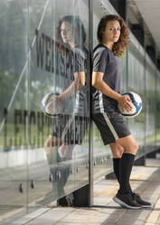 Female soccer player holding ball while standing by glass wall - STSF02611